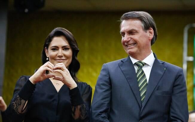 mulher fazendo coração com as mãos e homem ao lado dela