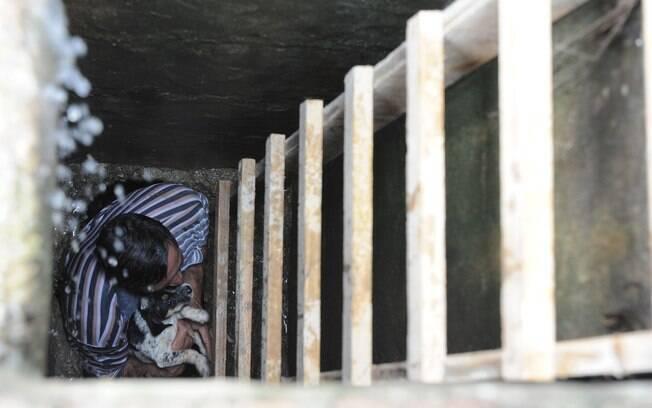 Técnico em refrigeração Samir Dutra entra no bueiro para salvar o cachorro