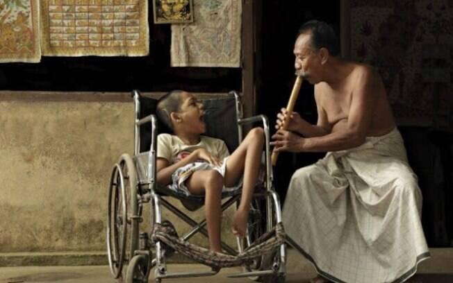 Morador de Bali toca flauta de bambu para distrair um garoto deficiente a quem ama como se fosse seu próprio filho, apesar de não o ser.