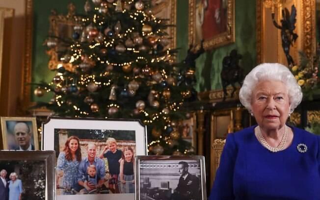 mulher na frente de árvore de natal e ao lado de porta retratos