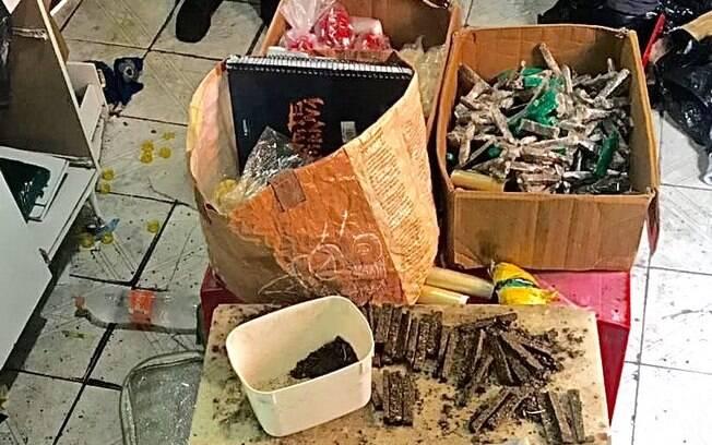 Dentro da sacola de papelão à esquerda, foi encontrado um caderno preto, um dos grandes prêmios desta apreensão. Sem tempo de reagir os criminosos deixaram para trás o livro caixa do tráfico contendo detalhes de quantidades, valores, nomes e locais ligados ao comércio da morte. Note as péssimas condições de higiene do local