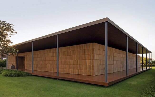 A casa de 918 m², também em Porto Feliz, São Paulo, tem pilares estreitos e numerosos para garantir a sustentação. Os painéis em ripas camuflam as portas do imóvel