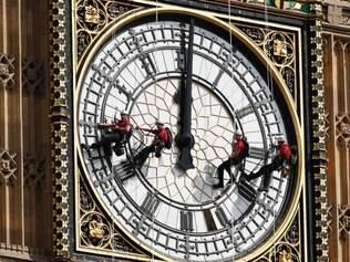 Técnicos trabalham na limpeza do relógio