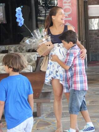 Miguel faz carinho na barriga da mãe, Nivea Stelmann, que está à espera de Bruna
