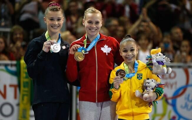 A pequenina Flavia Saraiva ao lado da medalhista de ouro Ellie Black e da medalhista de prata Madison Desch, no individual geral