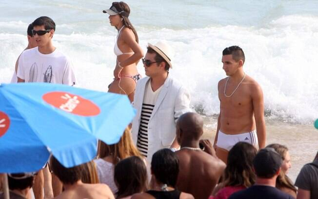 Eduardo Sterblitch grava na areia da praia cercado de banhistas