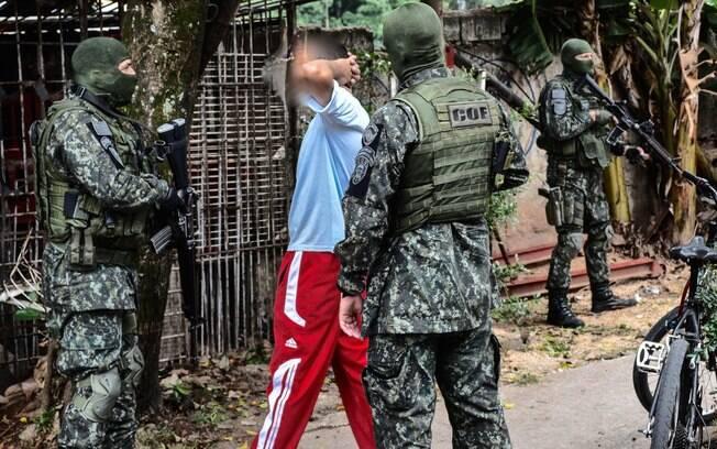 Equipe de Policiais Militares do Comandos e Operações Especiais, revista um suspeito