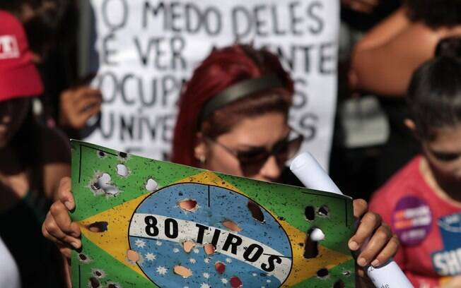 Em Brasília, manifestante levou cartaz lembrando morte de músico e de catador em ação do Exército no Rio de Janeiro