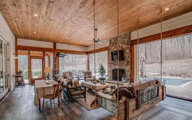Um dos cômodos, que faz parte da varanda da casa, é cercado por janelas e tem até um balanço rústico de madeira e cordas
