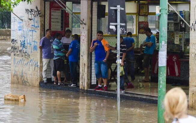 Pedestres se abrigam em bar para fugir de alagamento ao lado do Terminal Bandeira, nesta sexta