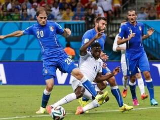 England's Danny Welbeck (11) falls between Italy's Gabriel Paletta (20) and Andrea Barzagli during the group D World Cup soccer match between England and Italy at the Arena da Amazonia in Manaus, Brazil, Saturday, June 14, 2014. (Antonio Calanni)