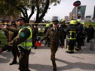 Police officer direct the curious away from a blast site as fire fighters stand by, at a subway station in Santiago, Chile, Monday Sept. 8, 2014. A bomb exploded in the Chilean subway station injuring at least seven people, the most damaging in a string of bombs planted around the country's capital this year. (AP Photo/ Luis Hidalgo)