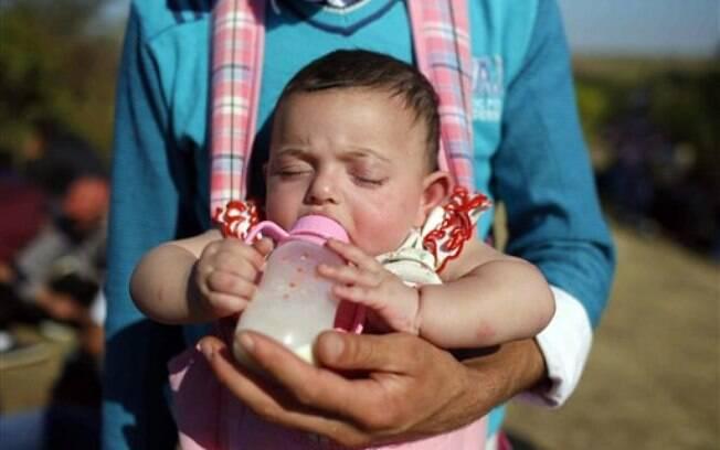 Homem alimenta bebê enquanto imigrantes refugiados tentam chegar à Europa