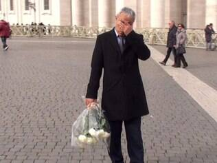 This handout photo grabed from a video made and released by ADNKRONOS on December 27, 2014 shows Mehmet Ali Agca, the Turkish former extremist who attempted to assassinate Pope John Paul II in 1981, holding a wreath of flowers on St. Peter's square in The Vatican. Ali Agca on December 27 laid flowers on the Pope John Paul II's tomb.