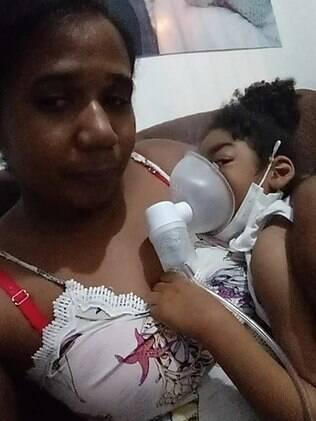 criança sentada no colo da mãe enquanto faz inalação