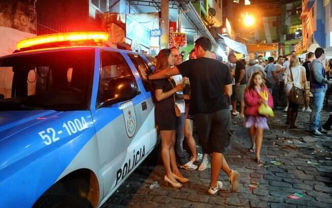 Casais namoram encostados em uma viatura da Unidade de Polícia Pacificadora da PM do Rio