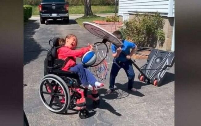 Irmão ajudando a irmã no basquete