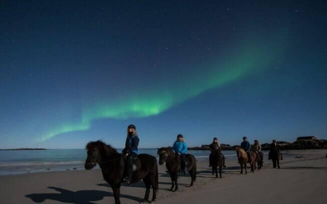 Entre as atrações turísticas da Noruega, está cavalgar enquanto admira o fenômeno conhecido como aurora boreal