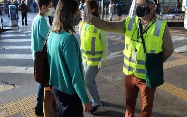 Profissionais medem a temperatura de passageiros no terminal central de Campinas