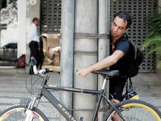 Improviso.  Fabiano Fonseca mostra que em muitos locais os postes são inviáveis para prender a bike