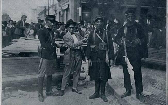 À esquerda o tenente João Cabanas entrega ao tenente Olímpio as divisas de cabo, condecorando um soldado, na ocupação do Palácio Campos Elíseos, no centro da Capital