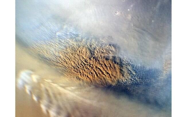 As nuvens são de uma tempestade de areia em Marte. Cientistas estudaram este tipo de fenômeno para determinar o melhor local e a forma ideal de pouso do Curiosity