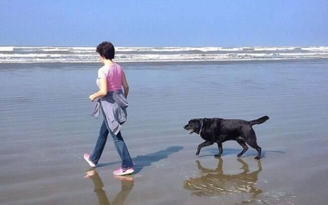 dona andando ao lado de cão-guia na praia