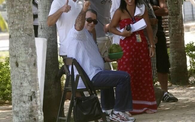 Tony Ramos acena para fotógrafo enquanto se refresca com água de coco