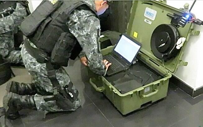 Membros do Esquadrão Antibomba preparam o centro de comando e controle desta crise. O equipamento que o PM do GATE está manipulando irá receber as imagens de raio-x da bomba e fazer análises detalhadas da sua composição e construção