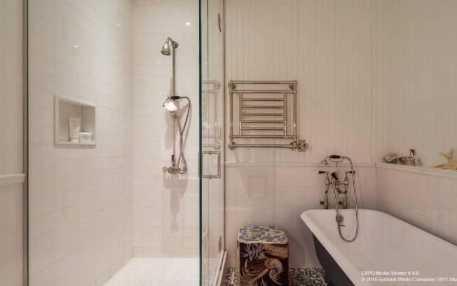 Azulejos hidráulicos e coloridos quebram o branco do restante do banheiro