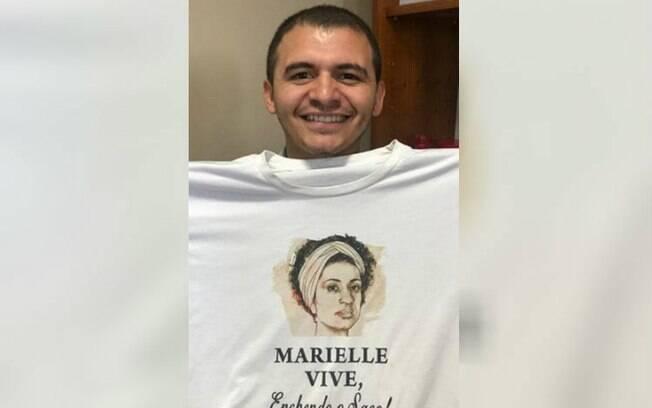 homem sorrindo e segurando camisa
