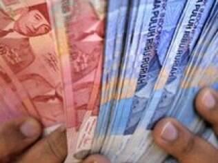 Mulher conta dinheiro local