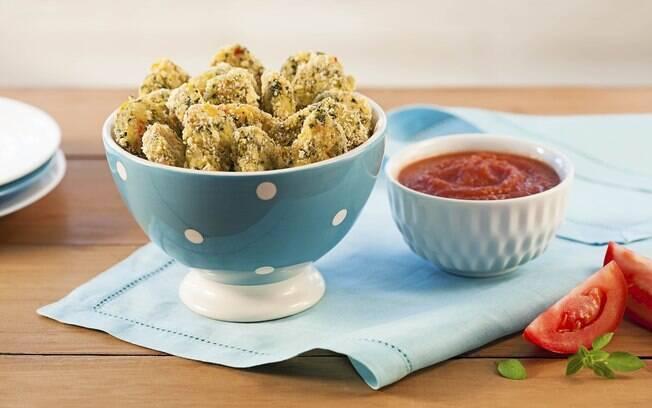 Nuggets em uma tigela, acompanhados de molho de tomate.