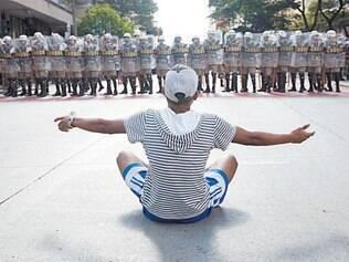 Isolado. Manifestante sentado na rua, na praça Sete, em frente ao pelotão da tropa de choque da PM