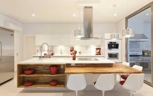 Integrada à sala de jantar, cozinha da arquiteta Mari possui ilha com bancada de madeira para aumentar o conforto e aquecer o ambiente