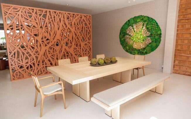 Os destaques do ambiente são as paredes feitas com pau a pique, técnica que consiste no entrelaçamento de vigas de madeira preenchidas com barro e os detalhes terrosos