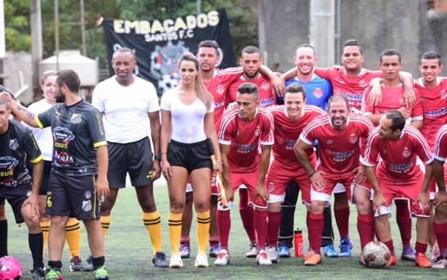 A bela bandeirinha Denise Bueno na foto com jogadores de várzea
