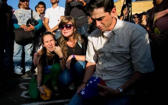 Estudantes choram durante vigília em Caracas por dois jovens mortos em confrontos violentos na Venezuela (13/2)