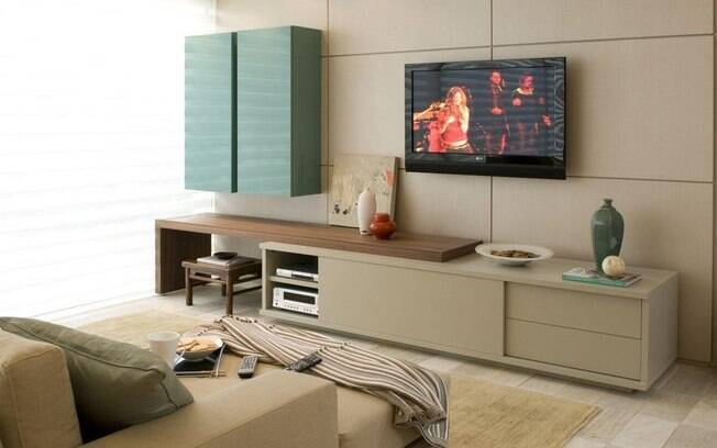 O painel instalado atrás da televisão permite esconder os fios e trazer conforto à decoração. Projeto da marca Segatto