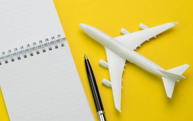 Miniatura de avião ao lado de bloco de notas e caneta sobre fundo amarelo