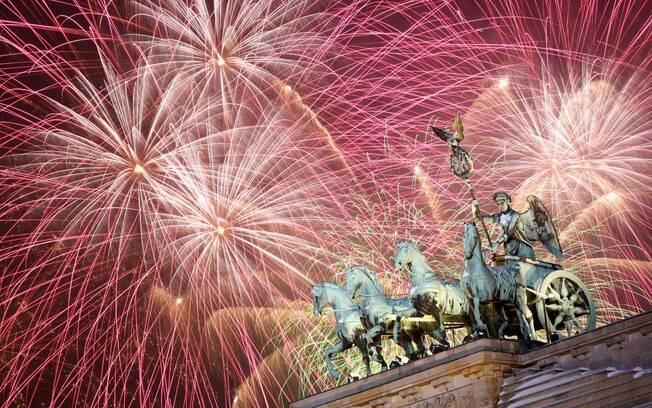 Fogos de artifício explodem sobre escultura do portão de Brademburgo; festa em Berlim se estende até altas horas da manhã