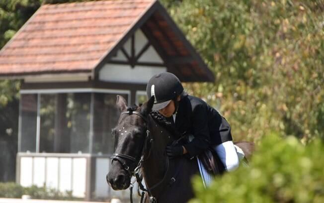 Aluno da escola no momento em que agradece com carinho seu cavalo pela boa atuação numa prova interna do clube
