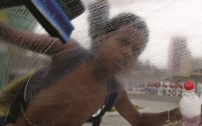 Criança se sustenta limpando para-brisas em frente à Favela do Lixão, no Rio de Janeiro