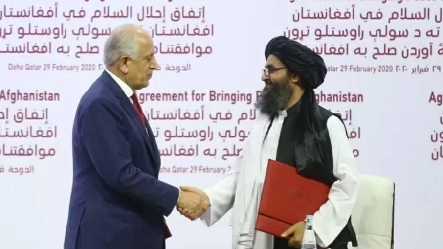 O enviado dos EUA, Zalmay Khalilzad e o líder talibã, Mullah Abdul Ghani Baradar, na assinatura do Acordo de Doha