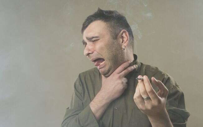 Homem engasgando com fumaça de cigarro após tragar