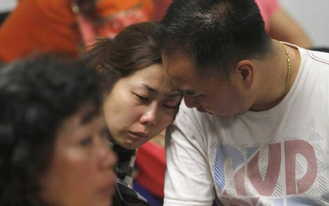 Parente dos passageiros do voo AirAsia QZ8501 chora enquanto espera notícias do avião desaparecido no aeroporto de Surabaya. Foto: AP Photo/Trisnadi