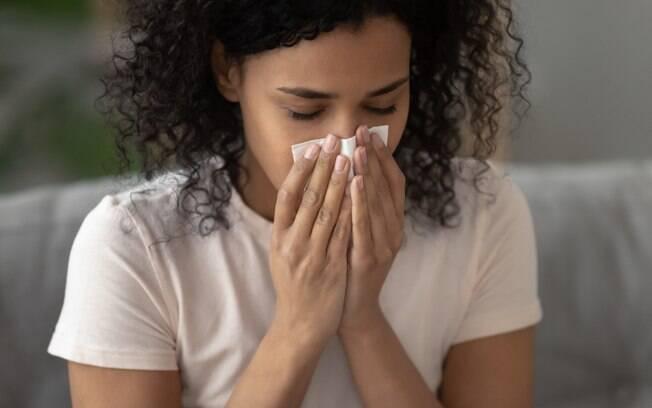 Mulher com lenço em frente ao nariz