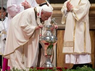 Pope Francis blows inside an amphora containing holy oil during a Chrism Mass in St. Peter's Basilica at the Vatican, Thursday, April 17, 2014.  During the mass the Pontiff blessed a token amount of oil that will be used to administer the sacraments throughout the year. The Chrism Mass marks the start of the Easter celebrations. (AP Photo/Andrew Medichini)