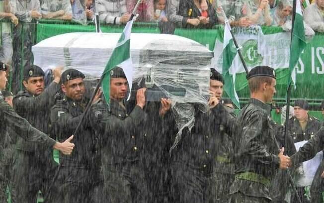 Sargentos do Exército Brasileiro carregam os corpos das vítimas da tragédia da Chapecoense, rodeados pela bandeira do clube