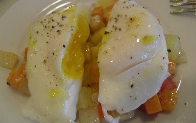 O ovo pochet perfeito sobre uma cama de legumes cozidos